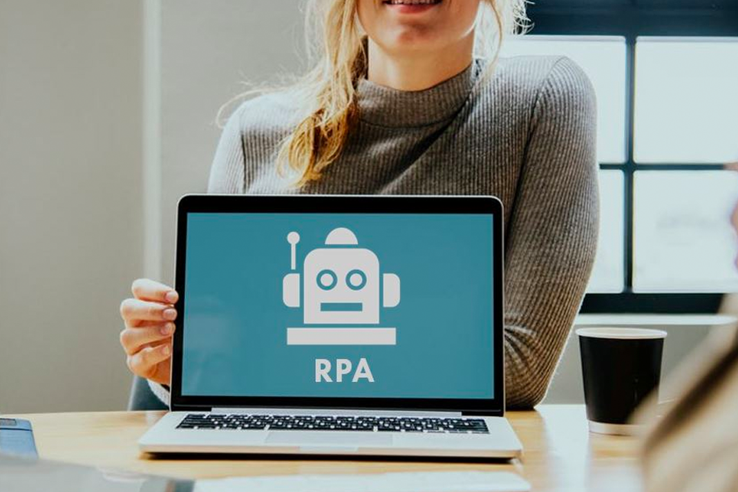 Woman at desk holding laptop with robot icon and RPA text on screen