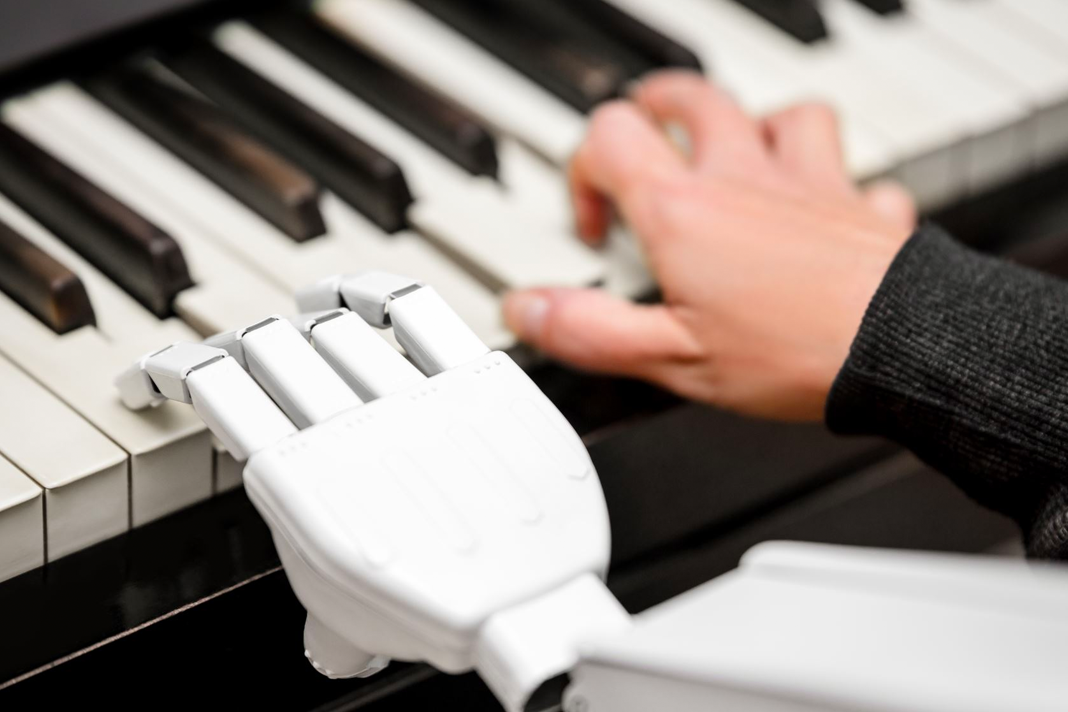 Close up of robotic hand alongside human hand playing piano